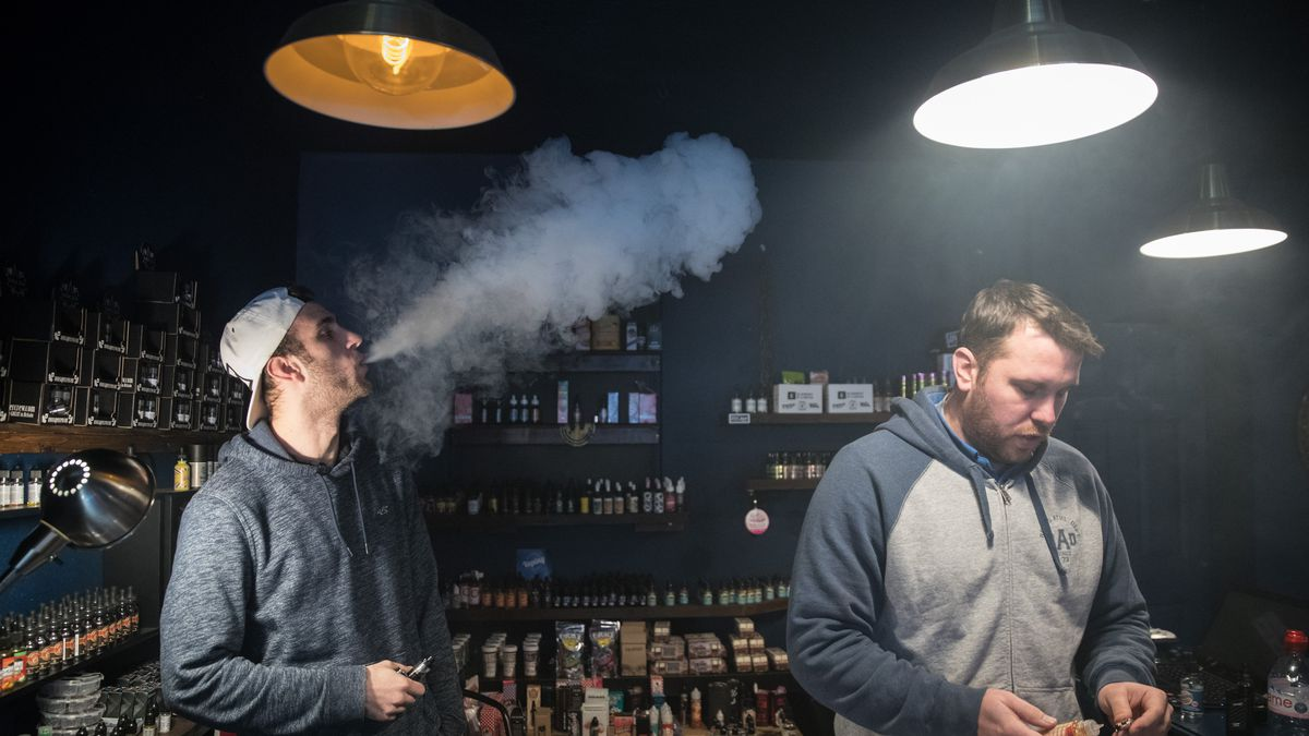 A man in a vaping shop blows smoke while another examines the wares.