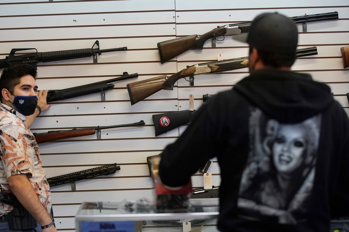 A worker shows guns to a customer at a gun shop. Saving the profits of the gun industry is clearly columnist Jacob Sullum's goal, a reader writes.