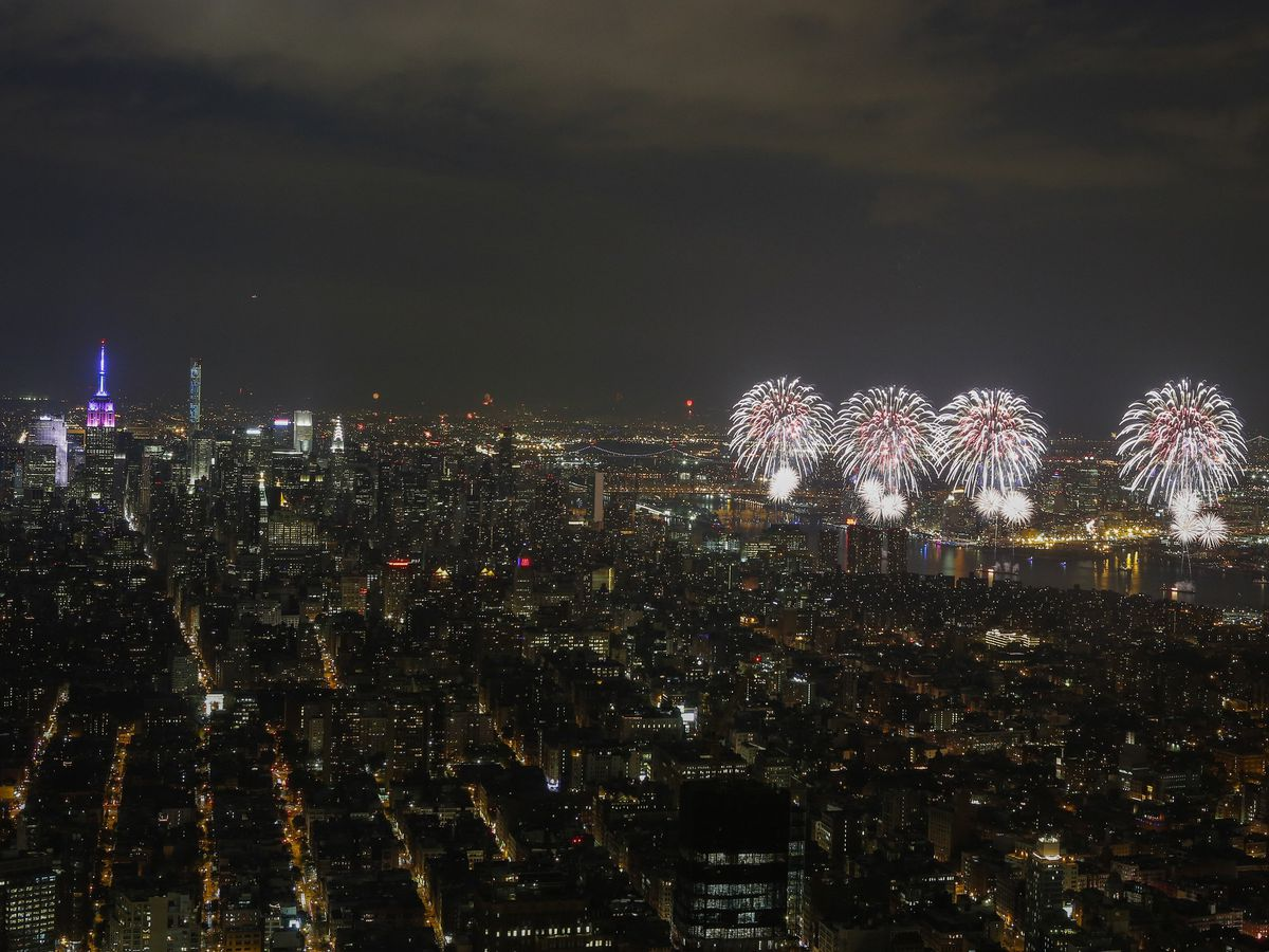 Multiple fireworks over the New York City skyline at night.
