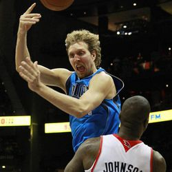 Dallas Mavericks power forward Dirk Nowitzki, top, is fouled by Atlanta Hawks forward Ivan Johnson (44) in the first half of an NBA basketball game on Thursday, April 26, 2012, in Atlanta.