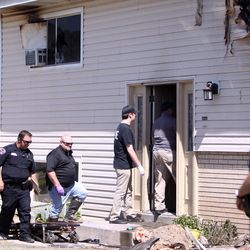 A medical examination team and other officials investigate a fatal fire that killed one woman in West Valley City on Monday, June 5, 2017.