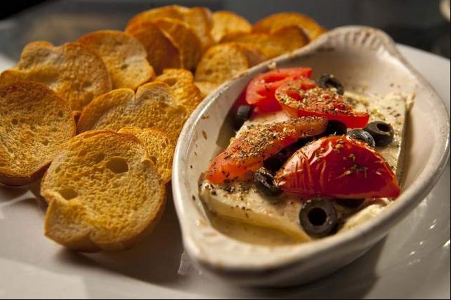 A dish of cheese topped with tomatoes and olives, on a larger plate with toasted bread