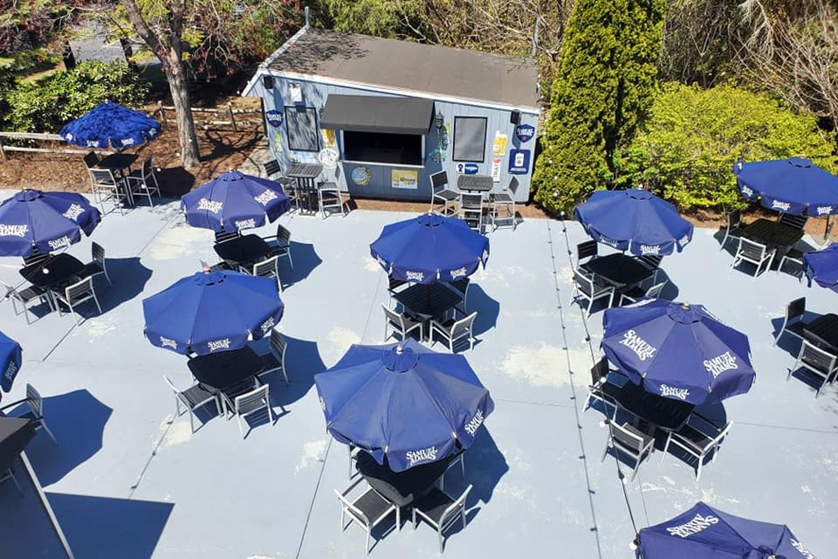 Overhead view of a restaurant patio. Dark blue Sam Adams-branded umbrellas stretch over a collection of four-top outdoor tables, spaced apart to help curb the spread of COVID-19 as restaurant service resumes.