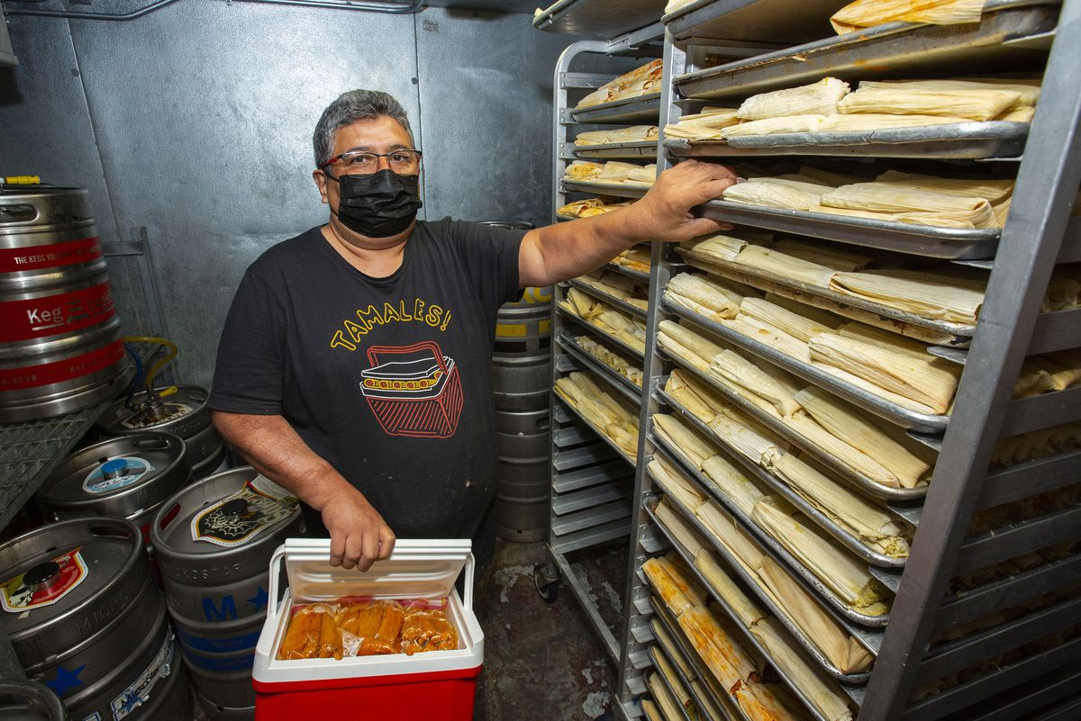A masked man standing next to a tray of tamales.