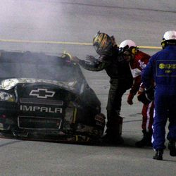 Ryan Newman exits his car near the pits after it caught fire during the NASCAR Sprint Cup Series auto race at Atlanta Motor Speedway, Sunday, Sept. 2, 2012, in Hampton, Ga.