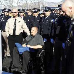 Sgt. Nate Hutchinson of the Weber County Sheriff's Office looks up at casket of Ogden officer Jared Francom after it was loaded onto a fire engine, en route to the Ogden Cemetery in Ogden Wednesday, Jan. 11, 2012. Francom and five others were injured during a routine drug raid on Jan. 4.