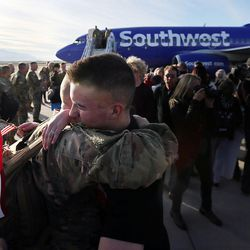 Sgt. Jim Booher hugs his son, Cody, front, as soldiers from Detachment 2, 101st Airborne Division (Air Assault) return to Utah on Friday, Nov. 18, 2016, following an 11-month deployment to Iraq.