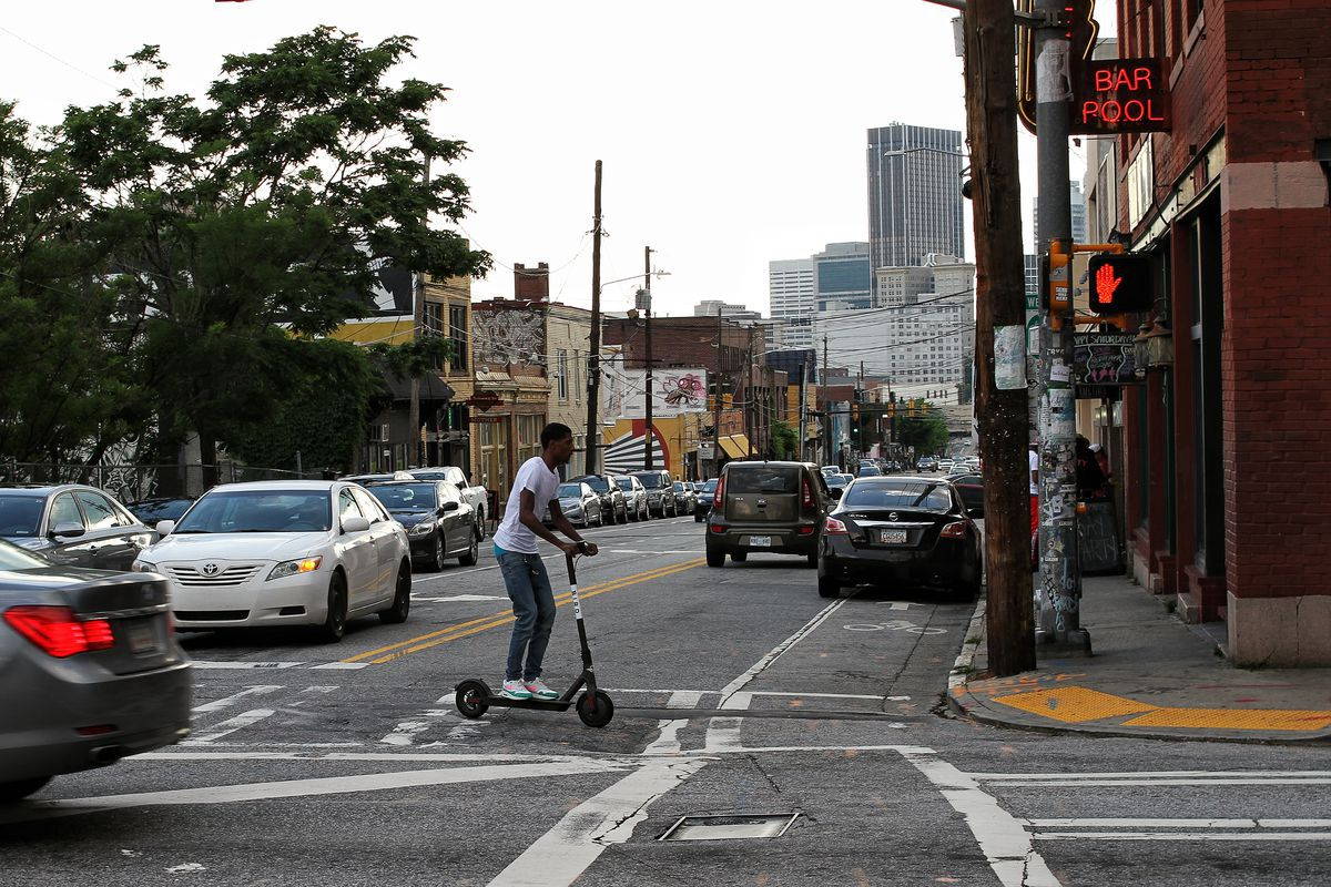 A photo of a man on an e-scooter crossing a street in Atlanta.