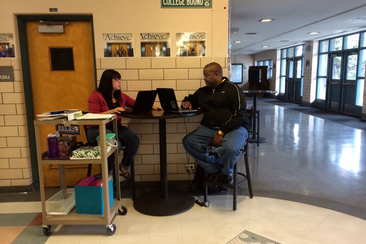 Kelle May-Garst, Kepner's English-language acquisition coach, and Chris Denmark, one of the school's assistant principals, work in the main hall of the school during classes. Denmark regularly works from the hall to keep an eye on the front door for parents and students.