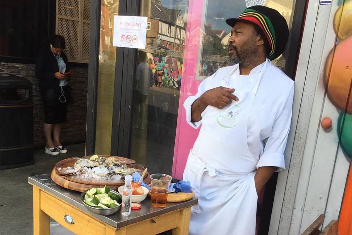 Christopher Smith stands outside his Tooting Market stall The Lone Fisherman, with a table of fresh oysters and Caribbean pepper sauces
