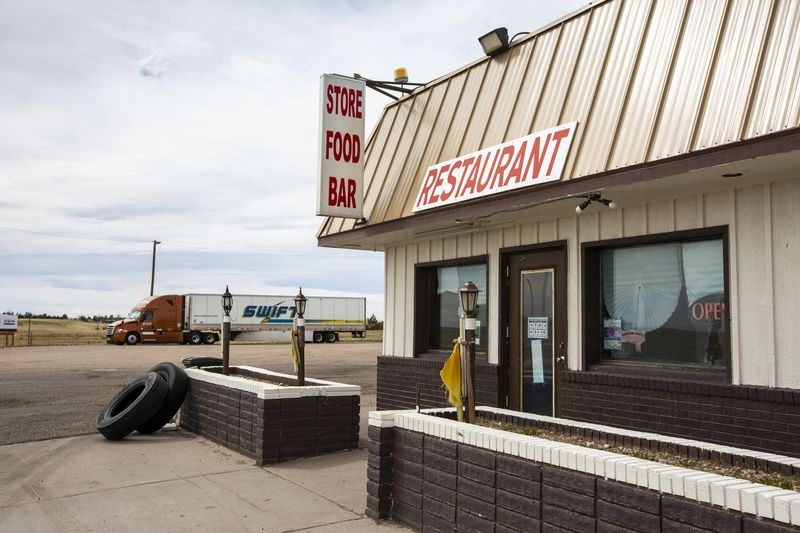 """Front corner of a building with a sign hanging from roof reading """"Store Food Bar."""" A separate sign on the roof reads """"Restaurant."""""""