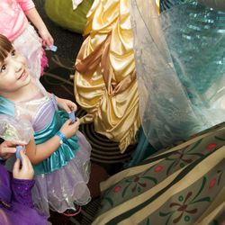 Zailee Zufelt, left, and Carley Zufelt, center, admire older princesses as they wait to get into Salt Lake Comic Con at the Salt Palace Convention Center in Salt Lake City, Thursday, Sept. 4, 2014.