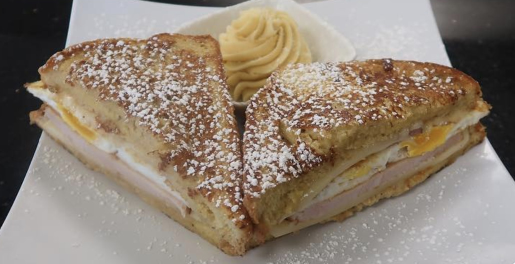 A sandwich with ham and eggs dusted with powdered sugar