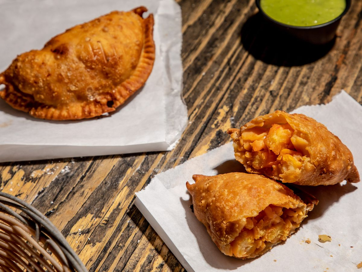 A golden Viagra empanada sits on wax paper, sliced in half, on the lower right-hand side of the photo, while a whole empanada lies on the upper left; a ramekin of green salsa sits in between