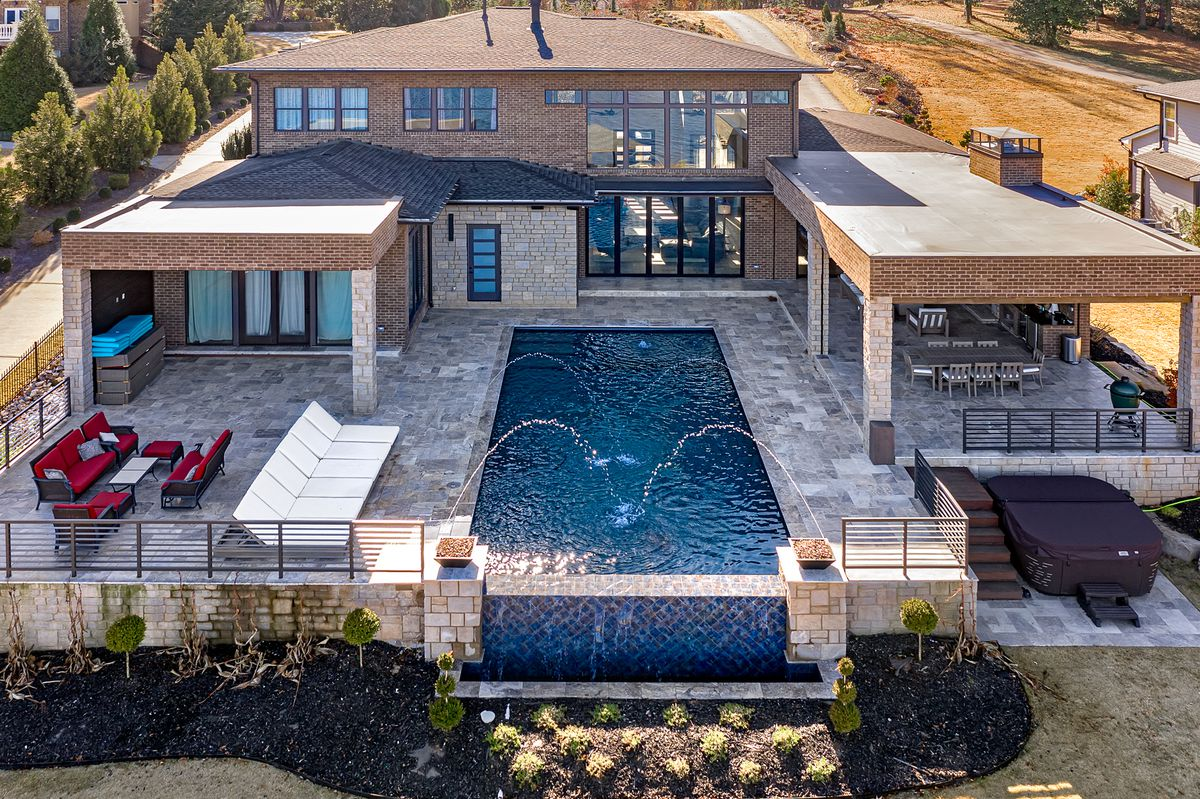 Rear view of house showing the pool deck, infinity pool and covered outdoor living room.