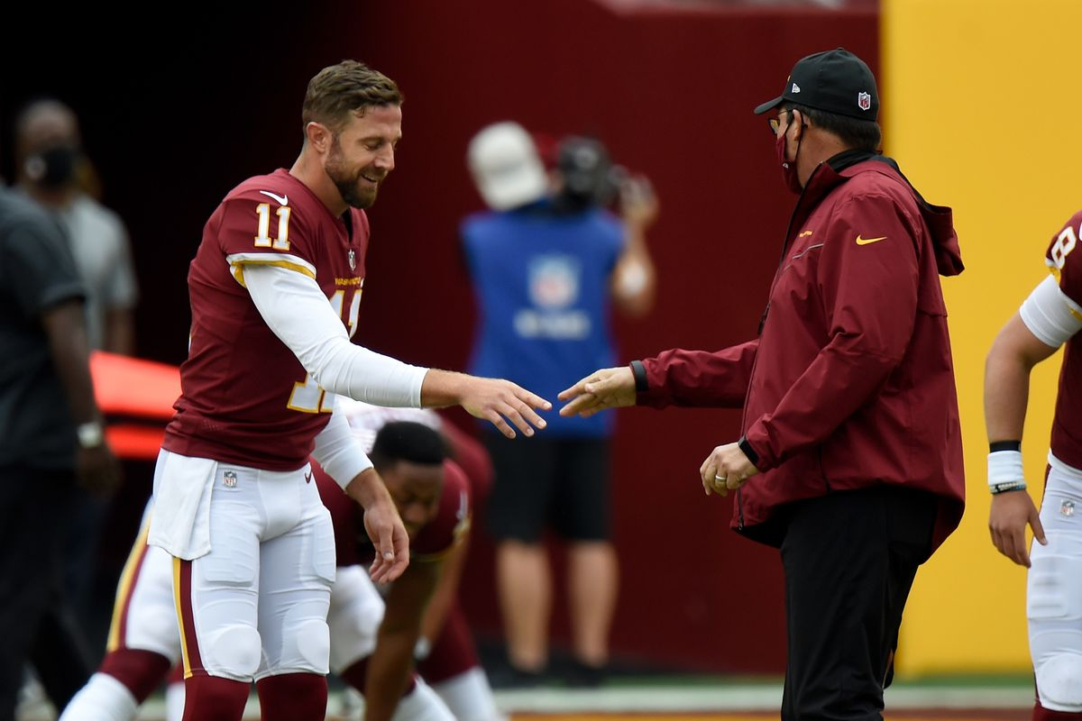 Alex Smith #11 of the Washington Football Team talks with head coach Ron Rivera before the game against the Los Angeles Rams at FedExField on October 11, 2020 in Landover, Maryland.