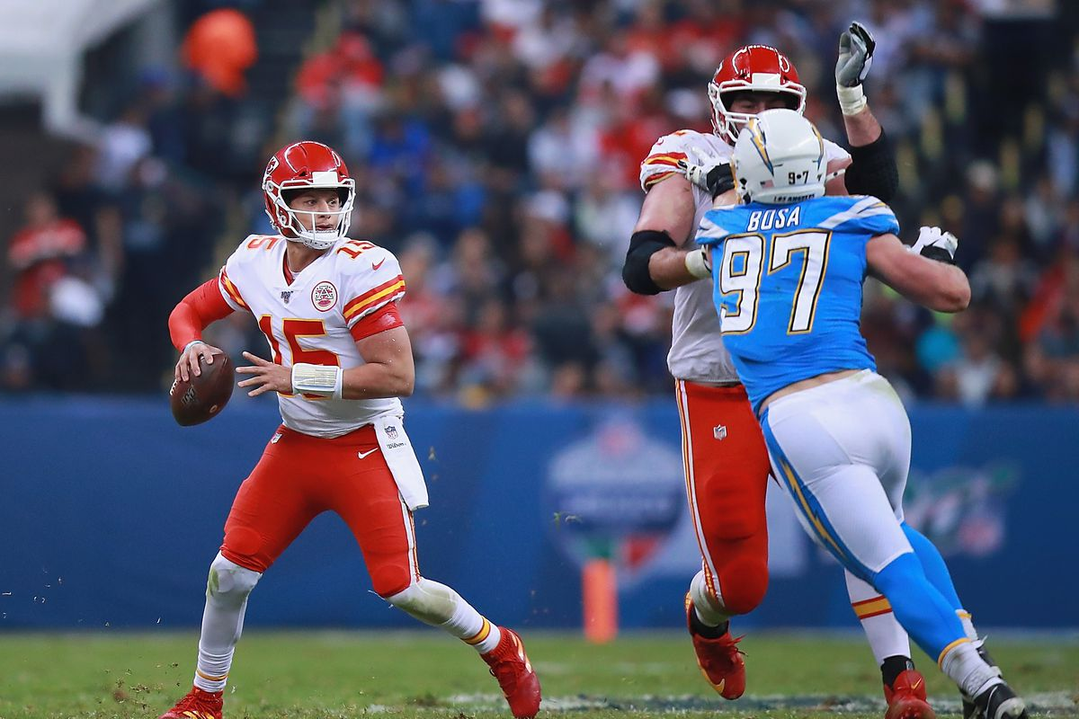 Quarterback Patrick Mahomes of the Kansas City Chiefs drops back to pass over defensive end Joey Bosa of the Los Angeles Chargers during the game at Estadio Azteca on November 18, 2019 in Mexico City, Mexico.