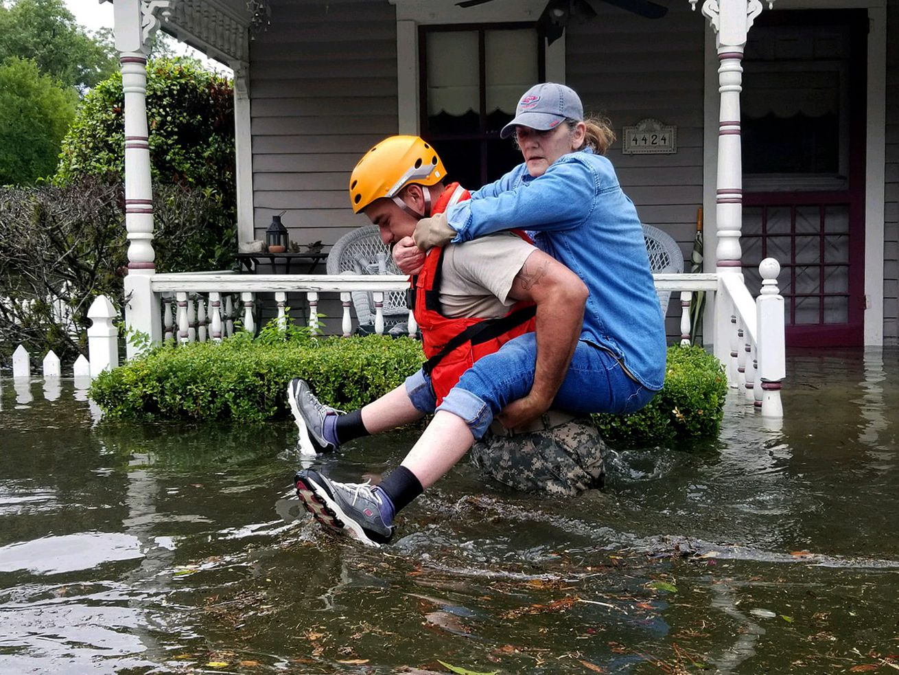A Texas National Guardsman carries a resident from her flooded home following Hurricane Harvey on August 27, 2017, in Houston, Texas.