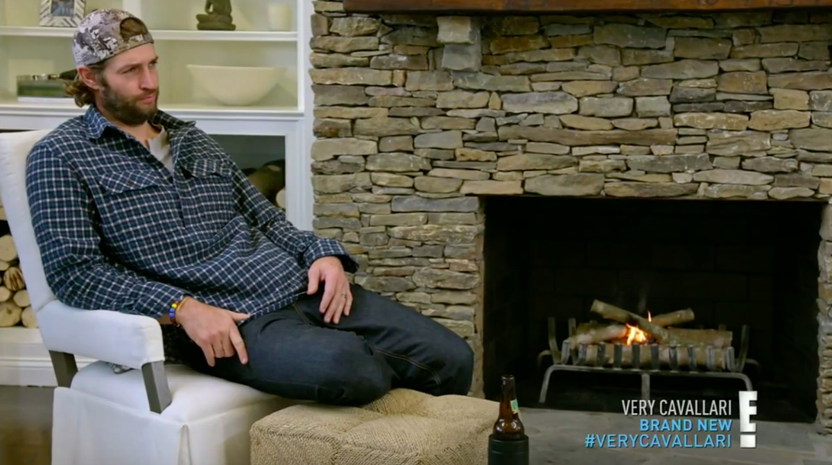 Jay Cutler sitting in front of a fireplace with a couple of tiny flames