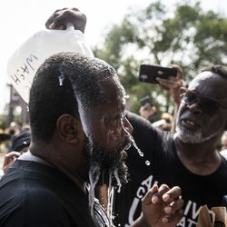 A man gets milk and water poured on his face after he was pepper sprayed while protesters were trying to enter the Kenosha Public Safety Building, Monday afternoon, Aug. 24, 2020. Protesters are gathered in downtown Kenosha, one day after police shot Jacob Blake.