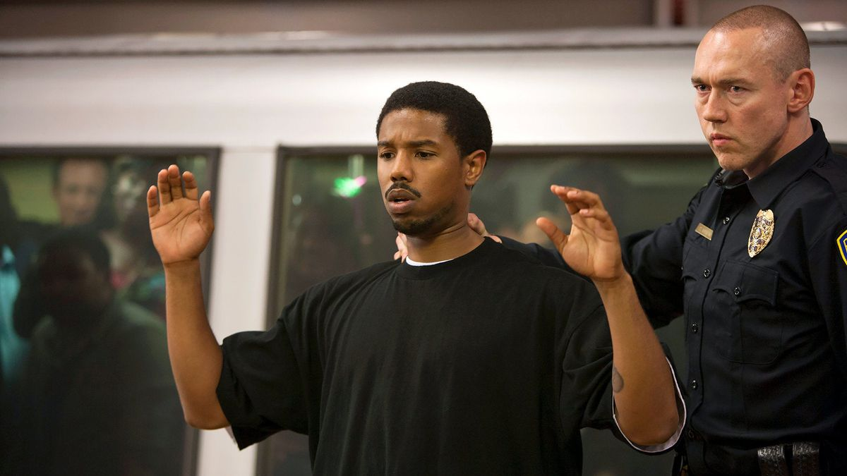 A white police officer (Kevin Durand) puts his hand on the neck of 22-year-old Black man Oscar Grant (Michael B. Jordan) in Fruitvale Station
