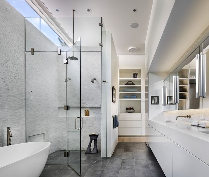 A bathroom with glass shower and white counters.