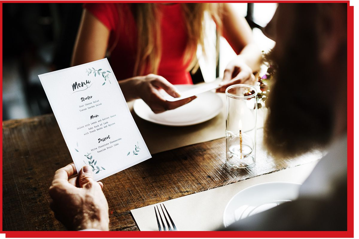 Man at restaurant table holds up a paper menu.