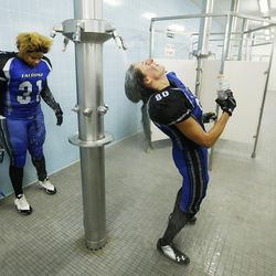 Utah Falconz players AJ Roby and Krisie Merrill cool off at half time against the Sacramento Sirens in Murray on June 27, 2015. The Falconz compete in a women's tackle football league.