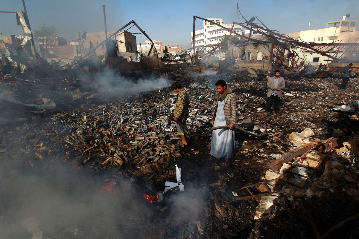 Yemeni men inspect the damage at the site of a Saudi-led coalition air strike which hit a sewing workshop, in the Yemeni capital of Sanaa, on February 14, 2016.