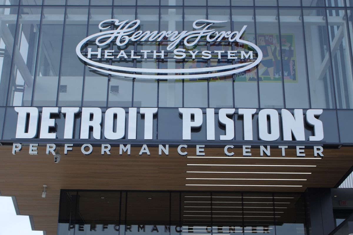 """A glass window with a block letters reading """"Henry Ford Health System Detroit Pistons Performance Center."""""""