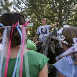 Griffin Reid, 11, wields a sword from atop of an armored horse statue during the Utah Renaissance Faire at Thanksgiving Point's Electric Park in Lehi on Friday, Aug. 23, 2019.