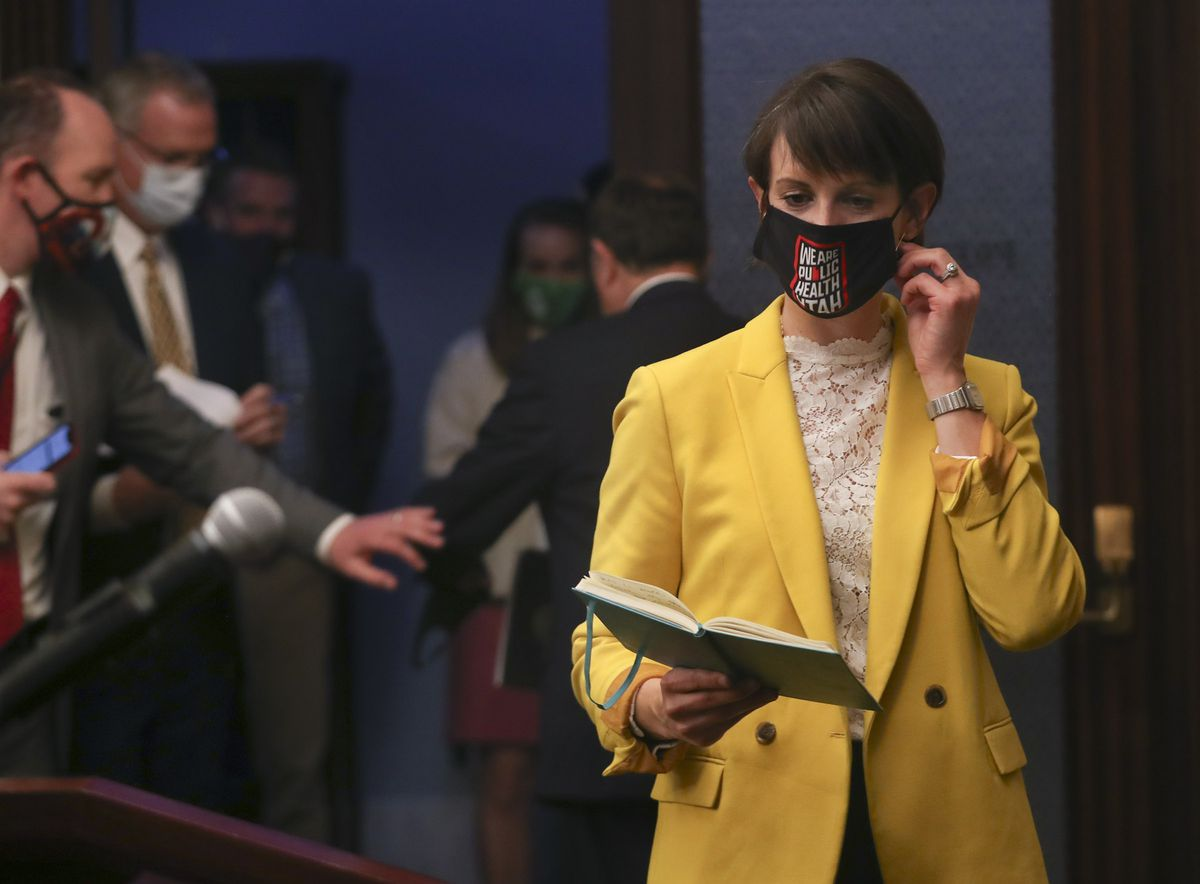 State epidemiologist Dr. Angela Dunn takes off her mask before talking about the pandemic and the number of positive COVID-19 cases in Utah during a briefing at the Capitol in Salt Lake City on Thursday, Dec. 17, 2020.