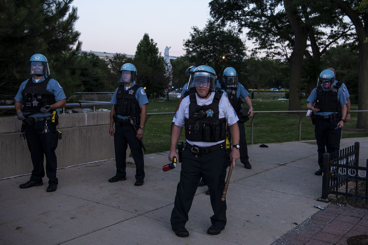 Chicago police are armed with batons and pepper spray near the Columbus statue in Grant Park on Friday.