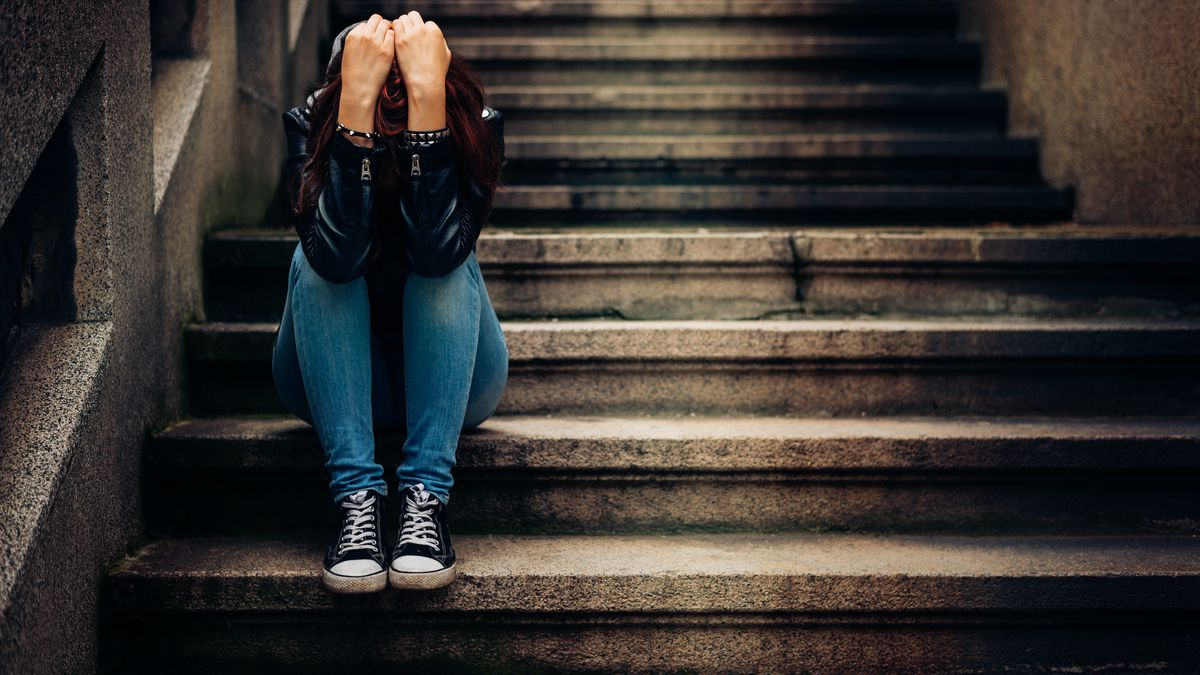 A young person wearing jeans and Converse-style shoes sits on concrete steps holding their head in their hands