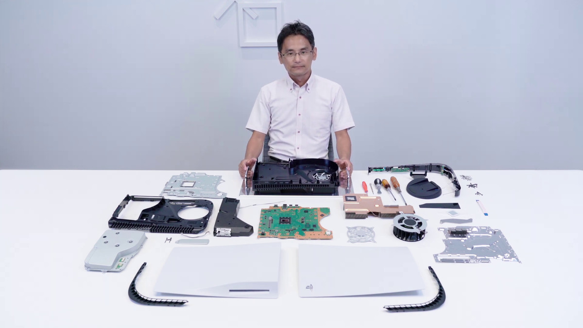 a Japanese man sitting at a white table with a disassembled PS5, with all its internal components arrayed on the table