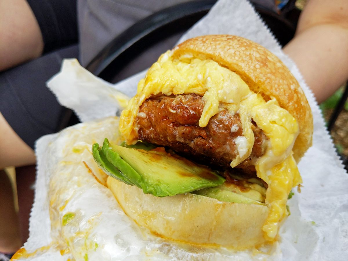 A round roll with scrambled egg, slced avocado and thick sausage patty, very messy.