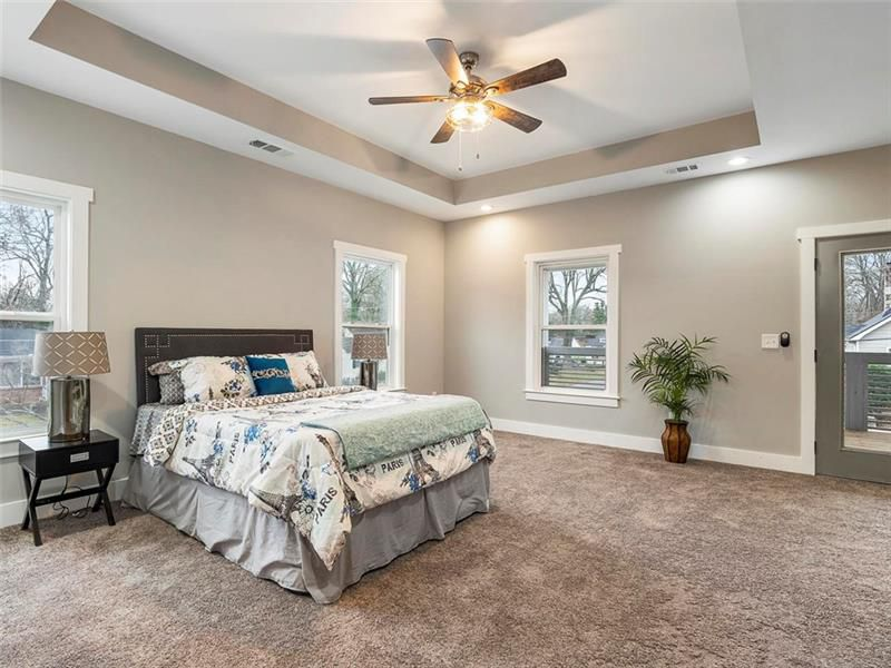 A big bedroom with carpet and a big bed.