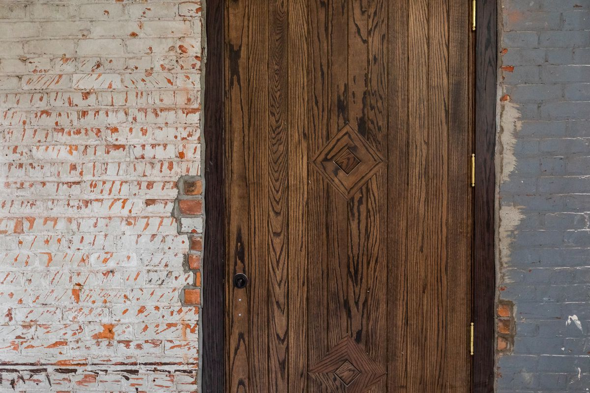 A heavy brown, planked oak door with a diamond pattern at the center is surrounded by a dark brown door frame with a whitewashed brick wall to the left and a blue painted brick wall on the right.