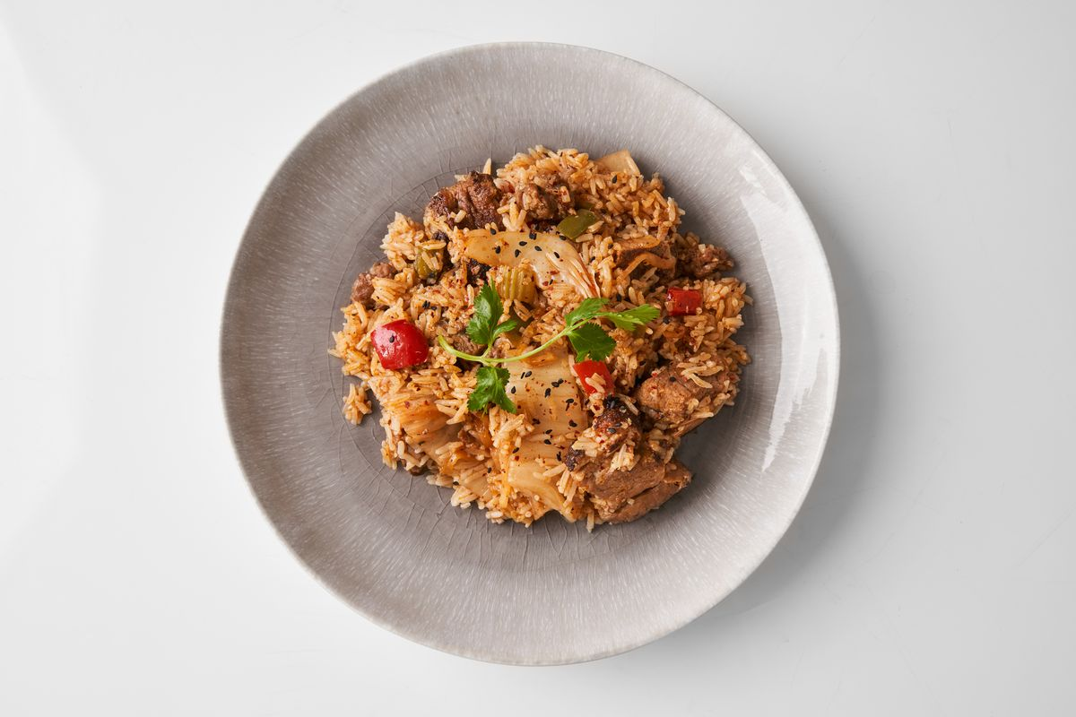 A beige plate with orange rice in it studded with some bright-red tomatoes