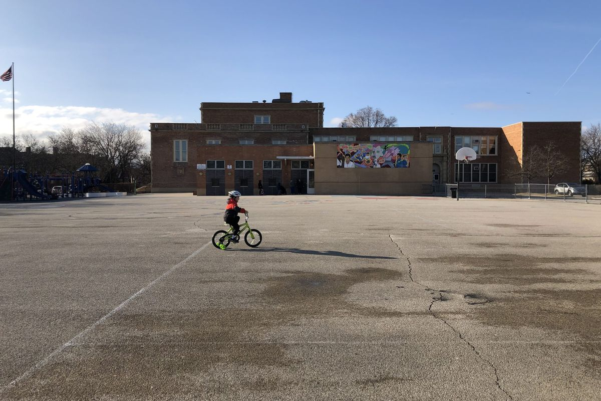 A child rides a bicycle at a shuttered Chicago public school the first week that campuses closed.