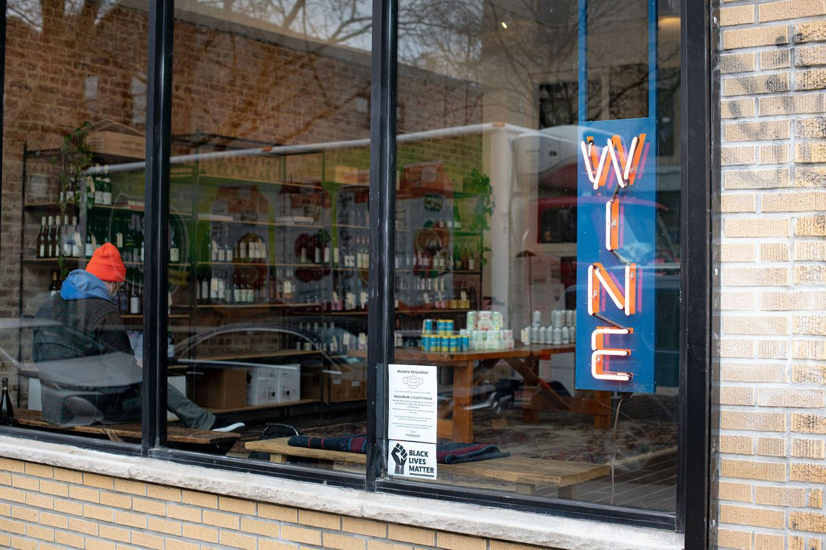 The exterior of a new wine store with a wine sign hanging in a clear glass window
