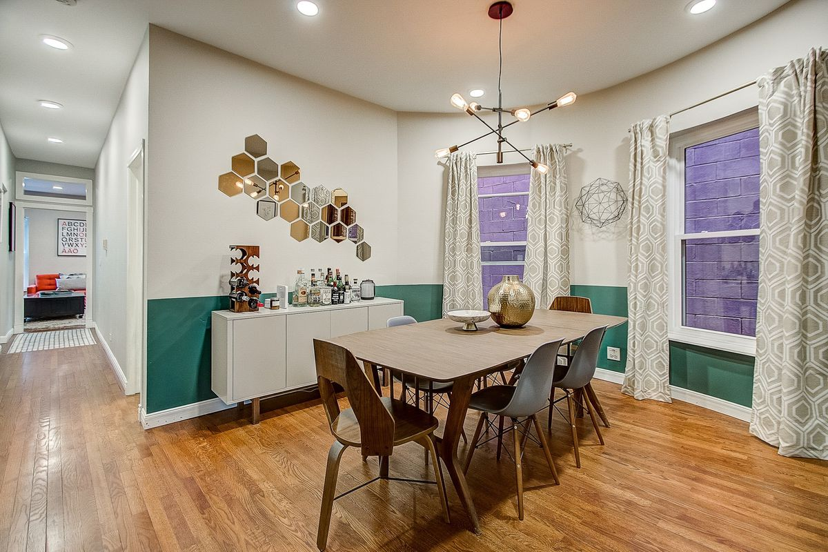 A dining room with a green accent wall and an industrial light fixture, bar, and dining table.