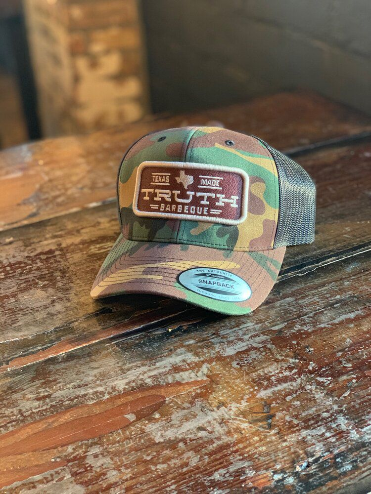 """A camouflage baseball cap with a """"Truth Barbeque"""" patch sewn on the front"""