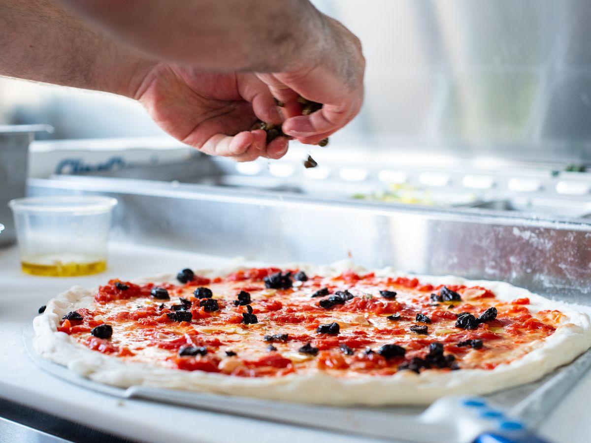 Chef Steve Samson builds a thin crust pizza at Superfine Pizza