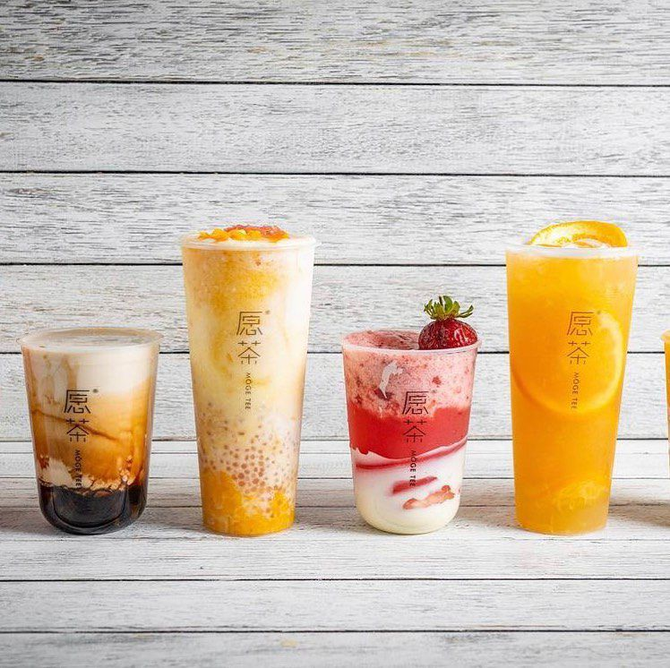 Four different tea beverages —an assortment of milk teas and fruit teas with cheese foam —are lined up on a light counter in front of a light wall.