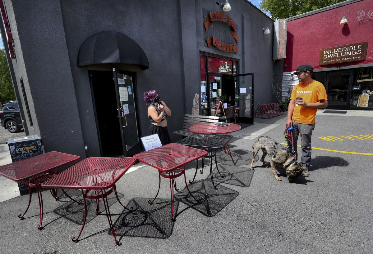 John Kennamer, a regular at Alchemy Coffee, stands back as he talks with barista Shalyn Karician outside the shop at 390 E. 1700 South in Salt Lake City on Wednesday, May 27, 2020.