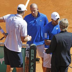 French team captain Guy Forget , center, shakes hand with U.S. player John Isner, left, as U.S. team captain Jim Courier, right, shakes hand with French player Jo-Wilfried Tsonga, after Isner defeated Tsonga, in the quarterfinal of the Davis Cup between France and U.S. in Monaco Sunday April 8, 2012.The U.S. team qualifies for the semi-final.