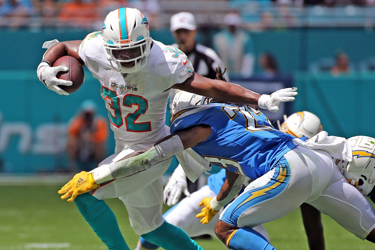 Miami Dolphins running back Kenyan Drake stiff-arms the Los Angeles Chargers' Rayshawn Jenkins in the second quarter at Hard Rock Stadium in Miami Gardens, Fla., on Sunday, Sept. 29 2019.