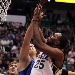 Al Jefferson of the Utah Jazz takes a shot while defended by Chris Kaman of the Dallas Mavericks during NBA basketball in Salt Lake City, Monday, Jan. 7, 2013. At left is Dirk Nowitzki of the Dallas Mavericks.