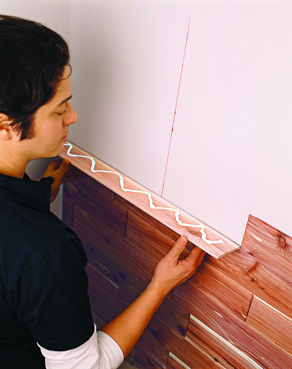 Person holding a cedar board up against the closet wall.